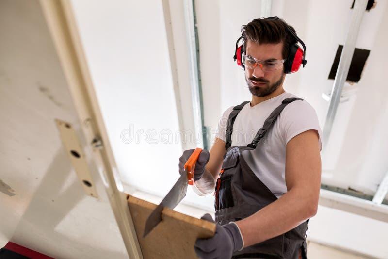 Aantrekkelijke mens die wat houtbewerking doen stock afbeeldingen
