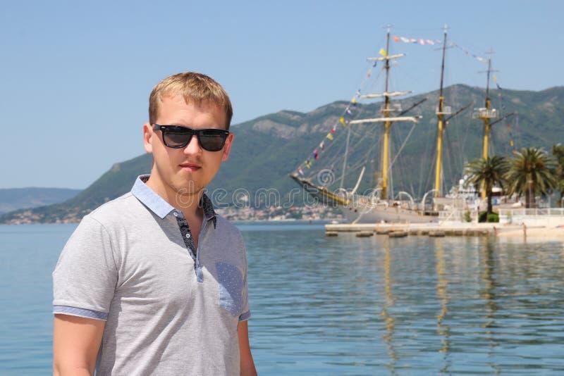 Aantrekkelijke mens en groot uitstekend jacht in haven van Tivat royalty-vrije stock afbeeldingen
