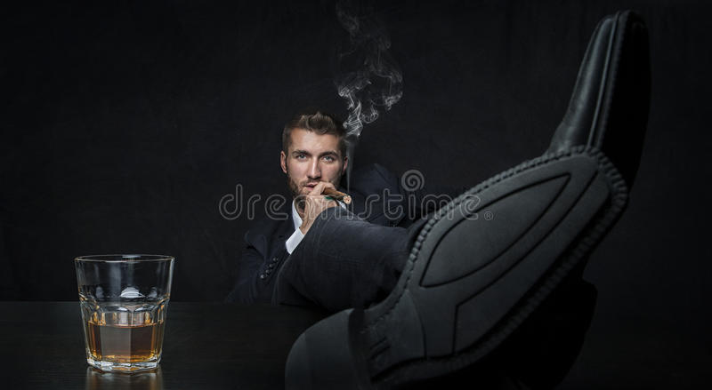 Aantrekkelijke mens met een glas van whisky en een sigaar stock foto's