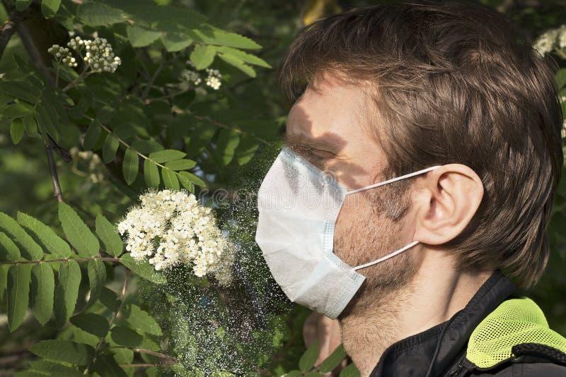 Aantrekkelijke mens met medisch masker op zijn gezicht, schaduw in zijn ogen tegen stuifmeelwolk stock foto