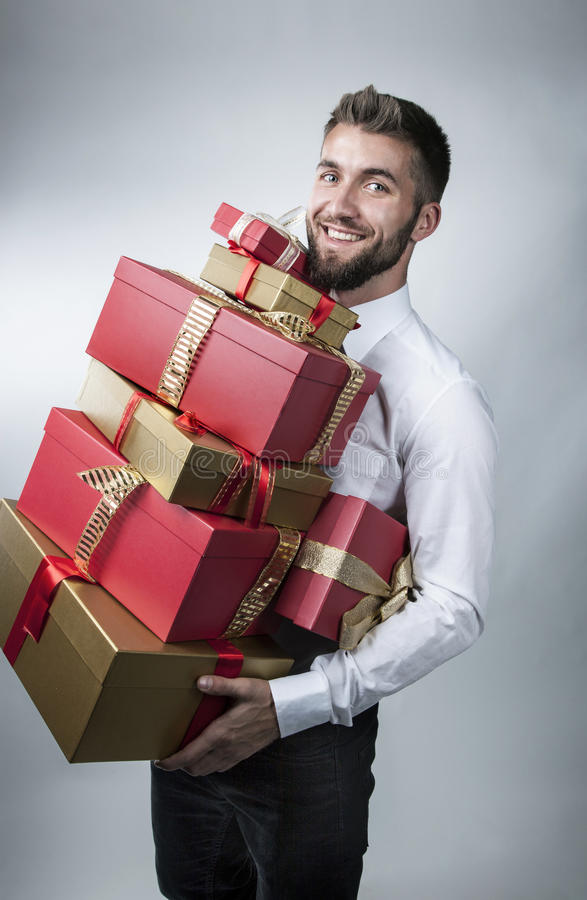 Aantrekkelijke mens met vele huidige dozen in zijn wapens stock fotografie