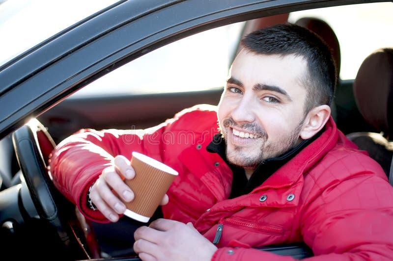 Aantrekkelijke mens in zijn auto het drinken koffie. stock afbeelding