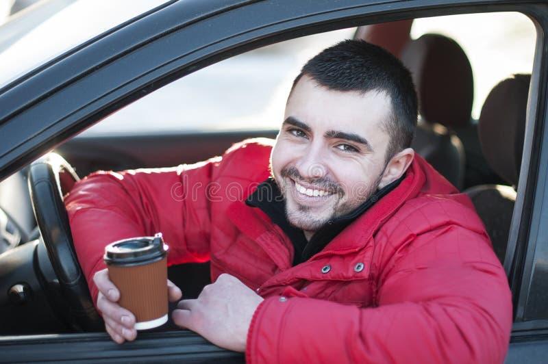Aantrekkelijke mens in zijn auto het drinken koffie. stock foto's