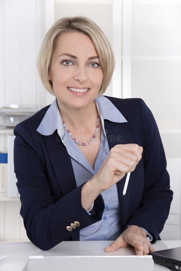 Aantrekkelijke midden oude vrouw in bedrijfsuitrustingszitting in haar o stock foto's