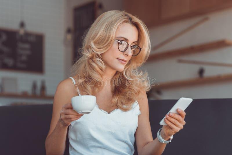 aantrekkelijke midden oude vrouw het drinken koffie en het gebruiken van smartphone stock foto's