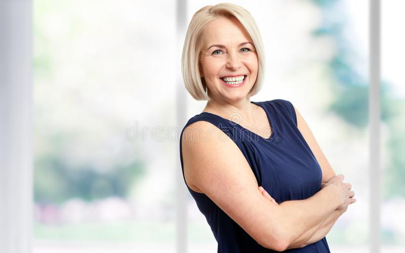 Aantrekkelijke midden oude vrouw met een mooie glimlach dichtbij het venster royalty-vrije stock fotografie