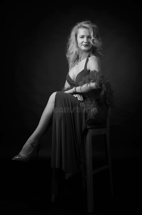 Aantrekkelijke middenleeftijdsvrouw in avondjurk met pluizige veerboa royalty-vrije stock afbeeldingen
