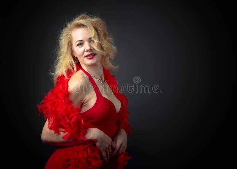 Aantrekkelijke middenleeftijdsvrouw in rode avondjurk met pluizige veerboa royalty-vrije stock afbeeldingen