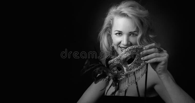 Aantrekkelijke middenleeftijdsvrouw in zwarte avondjurk met Carnaval-masker stock foto