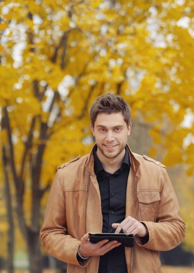 Aantrekkelijke modieuze jonge mens die een touchpad in de herfstpark gebruiken stock afbeeldingen