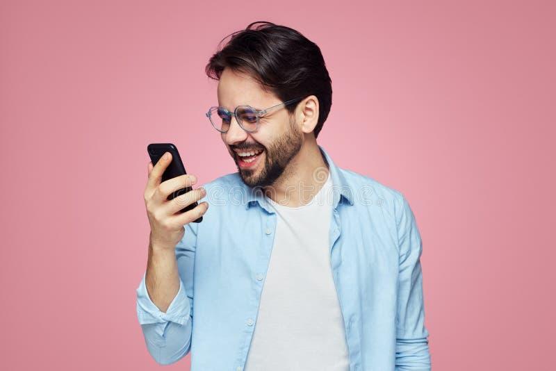 Aantrekkelijke modieuze mannelijk heeft gelukkige uitdrukking als ontvangen prettig bericht De Hipsterstudent geniet van online m stock fotografie