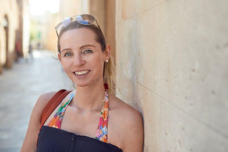 Aantrekkelijke modieuze vrouw die bij de camera glimlachen stock foto's