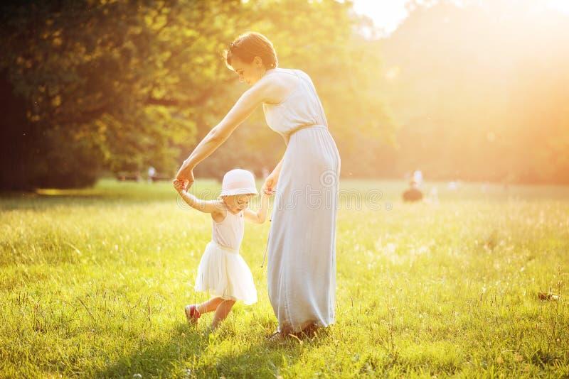 Aantrekkelijke moeder die met haar dochter op het gazon dansen royalty-vrije stock fotografie