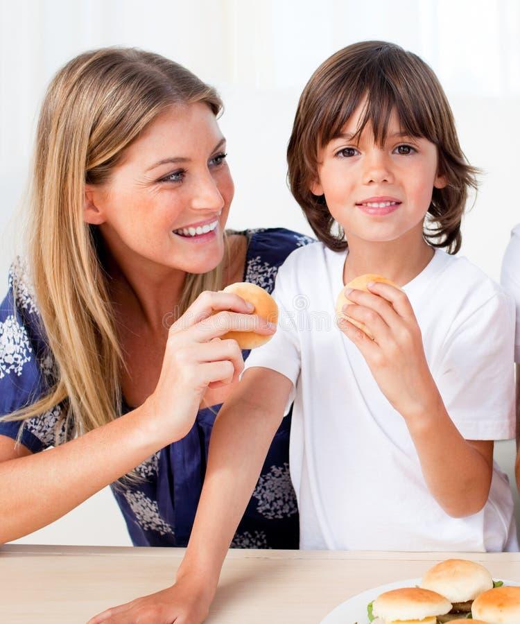 Aantrekkelijke moeder en haar zoon die burgers eten stock foto's