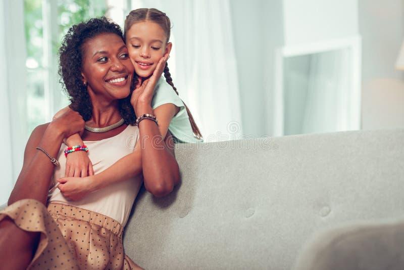 Aantrekkelijke moeder teder wat betreft het gezicht van haar kleine dochter stock foto's