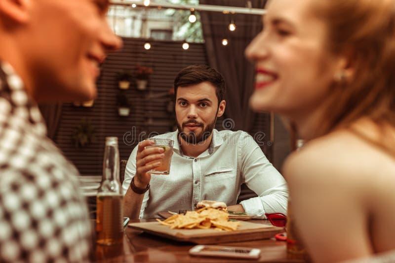Aantrekkelijke mooie aantrekkelijke mens die bij zijn flirtende vrienden staren royalty-vrije stock afbeelding
