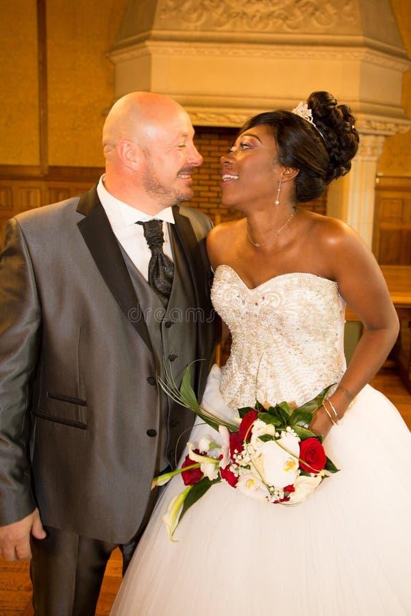 Aantrekkelijke multi rassenpaar Afrikaanse bruid en Amerikaanse Kaukasische bruidegom tijdens huwelijksviering stock afbeelding