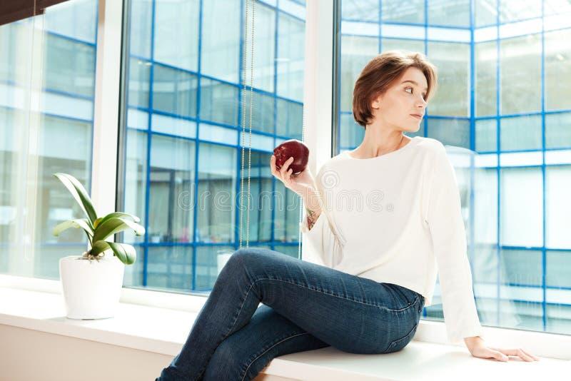Aantrekkelijke nadenkende jonge vrouwenzitting op venstervensterbank in bureau stock foto's