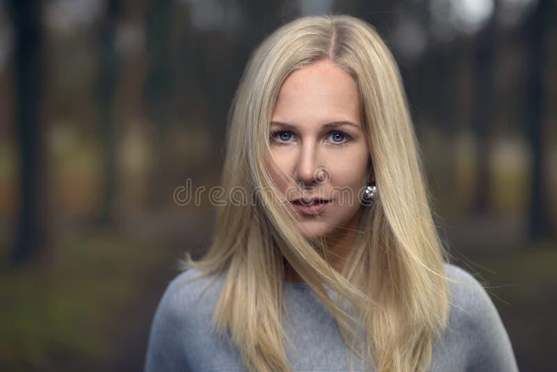Aantrekkelijke nadenkende modieuze blonde vrouw royalty-vrije stock afbeelding