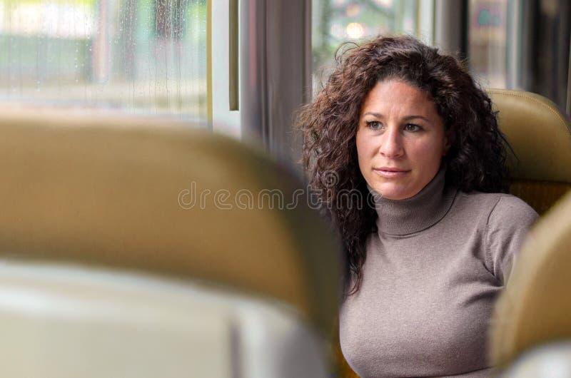 Aantrekkelijke nadenkende vrouw die door trein reizen stock afbeelding