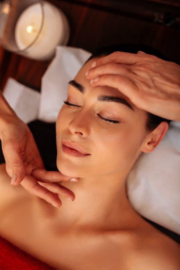 Aantrekkelijke onberispelijke vrouwelijke cliënt die in meditatieve massage worden geïmpliceerd royalty-vrije stock foto's