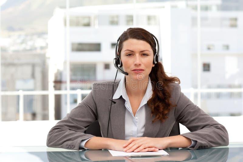 Aantrekkelijke onderneemster die gebruikend hoofdtelefoon spreekt royalty-vrije stock afbeeldingen