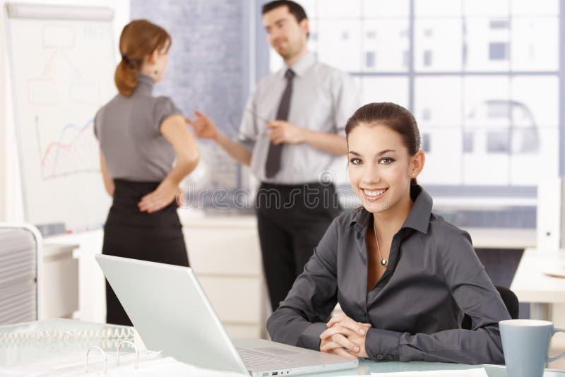 Aantrekkelijke onderneemster die gelukkig in bureau glimlacht stock afbeeldingen