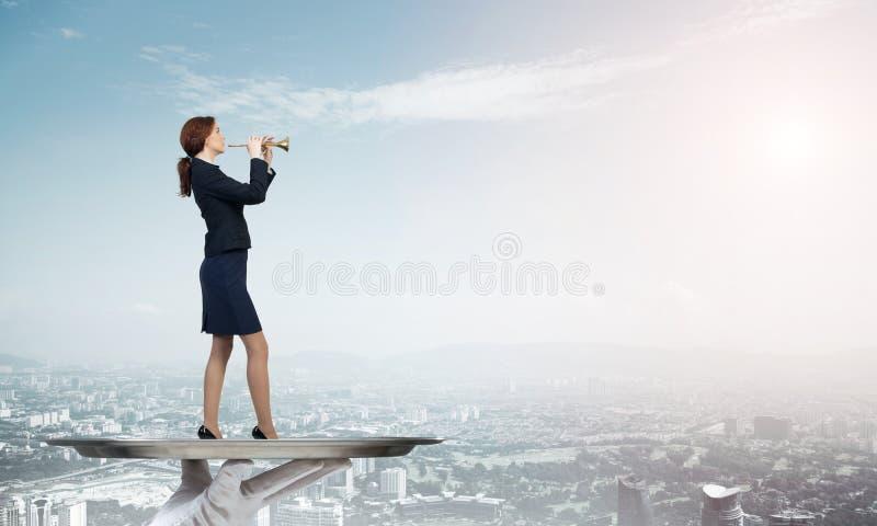 Aantrekkelijke onderneemster die op metaaldienblad Fife spelen tegen cityscape achtergrond royalty-vrije stock afbeelding