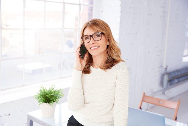 Aantrekkelijke onderneemster die telefoneren terwijl status in het bureau stock foto