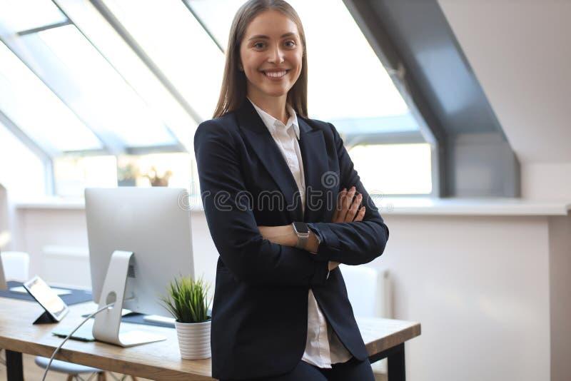 Aantrekkelijke onderneemster die zich dichtbij bureau in het bureau bevinden stock foto's