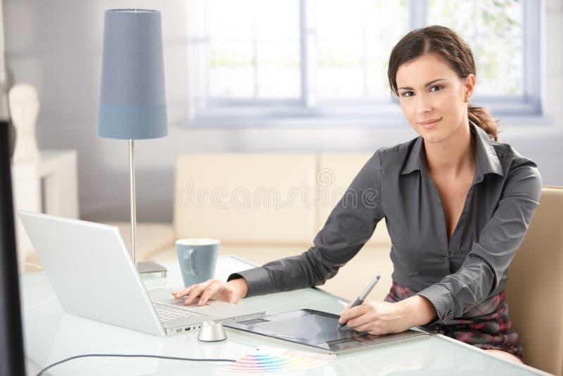 Aantrekkelijke ontwerper die tablet en laptop met behulp van