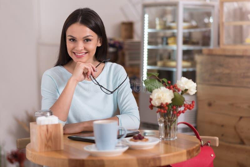 Aantrekkelijke opgetogen donkerbruine vrouw die een koffiepauze hebben royalty-vrije stock foto