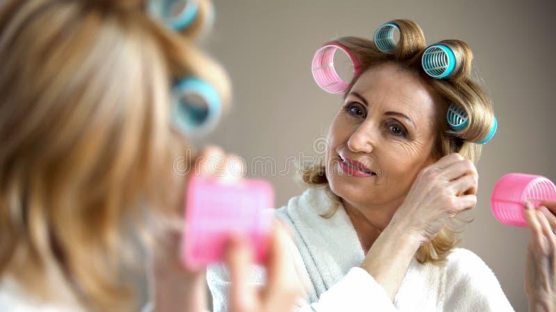 Aantrekkelijke oude dame die haarkrulspeld zetten en in spiegel, schoonheidstrucs glimlachen royalty-vrije stock afbeeldingen