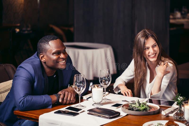Aantrekkelijke paar het besteden tijd tussen verschillende rassen samen in luxeryrestaurant stock foto's