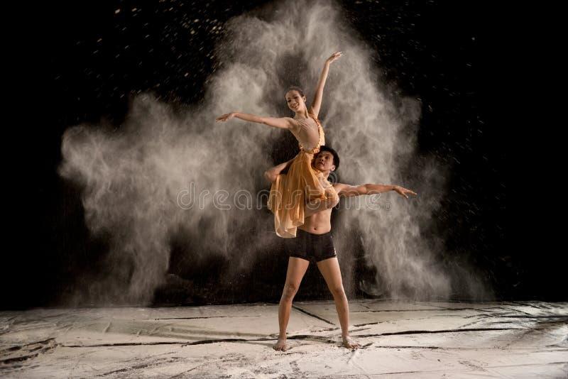 Aantrekkelijke paarballetdanser met wit poeder in de lucht royalty-vrije stock afbeeldingen