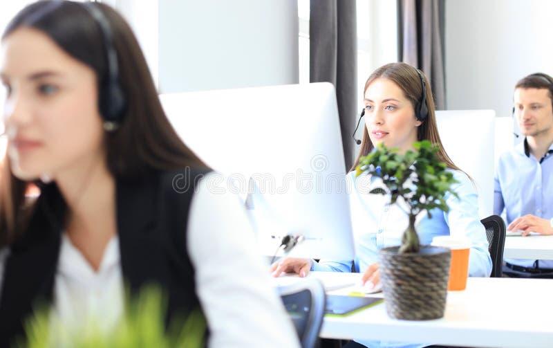 Aantrekkelijke positieve jonge zakenlui en collega's in een call centrebureau stock fotografie