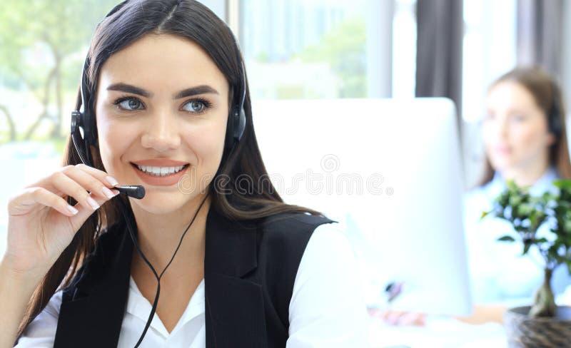 Aantrekkelijke positieve jonge zakenlui en collega's in een call centrebureau stock afbeeldingen