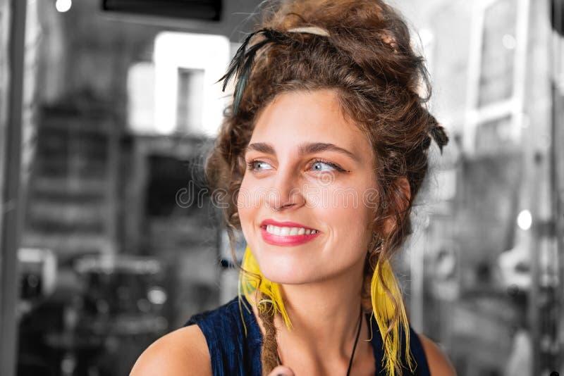 Aantrekkelijke richtende blauw-eyed vrouw die ruim terwijl vrolijk het voelen glimlachen royalty-vrije stock afbeelding