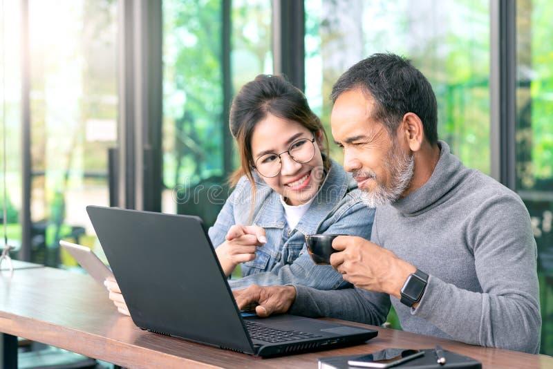 Aantrekkelijke rijpe Aziatische man die met witte modieuze korte baard laptop computer met de tiener binnen vrouw van oogglazen h stock afbeeldingen