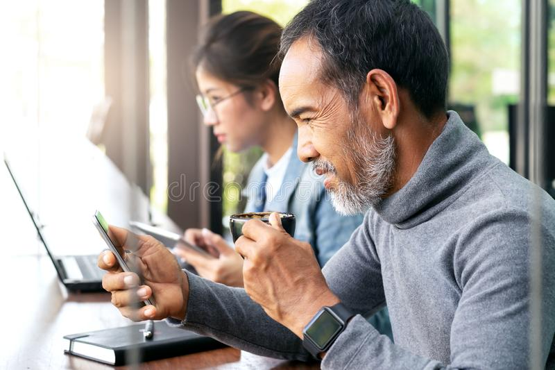 Aantrekkelijke rijpe Aziatische mens met witte modieuze korte baard die hispter het nieuws van de smartphonelezing of sociale med stock foto's