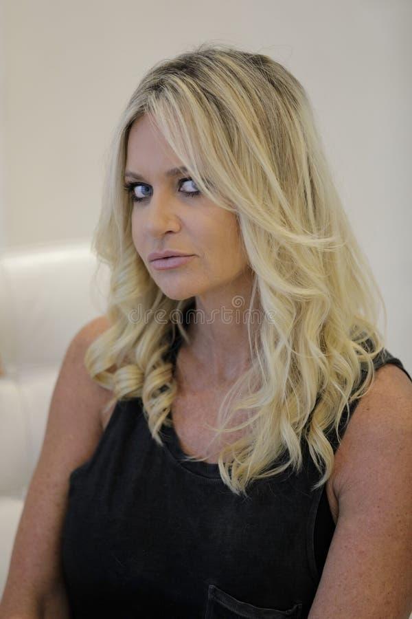 Aantrekkelijke rijpe blonde vrouw die camera bekijken royalty-vrije stock fotografie