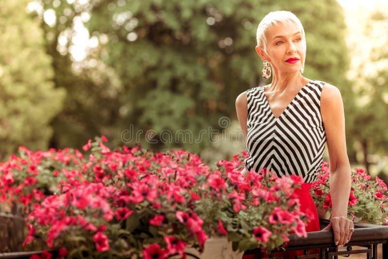 Aantrekkelijke rijpe vrouw die aardige oorringen dragen die zich op balkon bevinden royalty-vrije stock fotografie