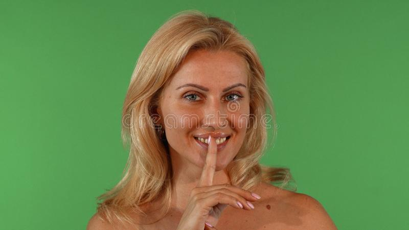 Aantrekkelijke rijpe vrouw die en aan de camera glimlachen doen zwijgen royalty-vrije stock afbeeldingen