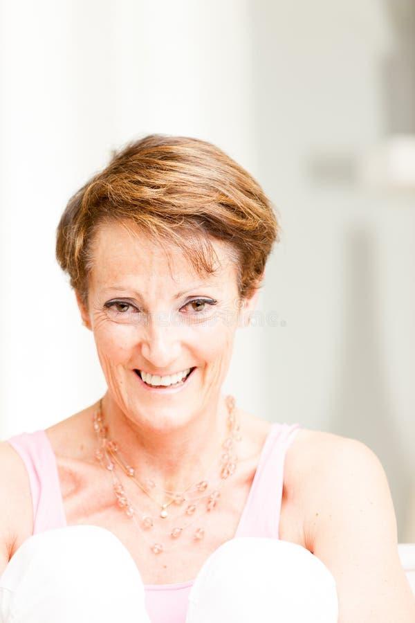 Aantrekkelijke rijpe vrouw met een levendige glimlach stock afbeelding