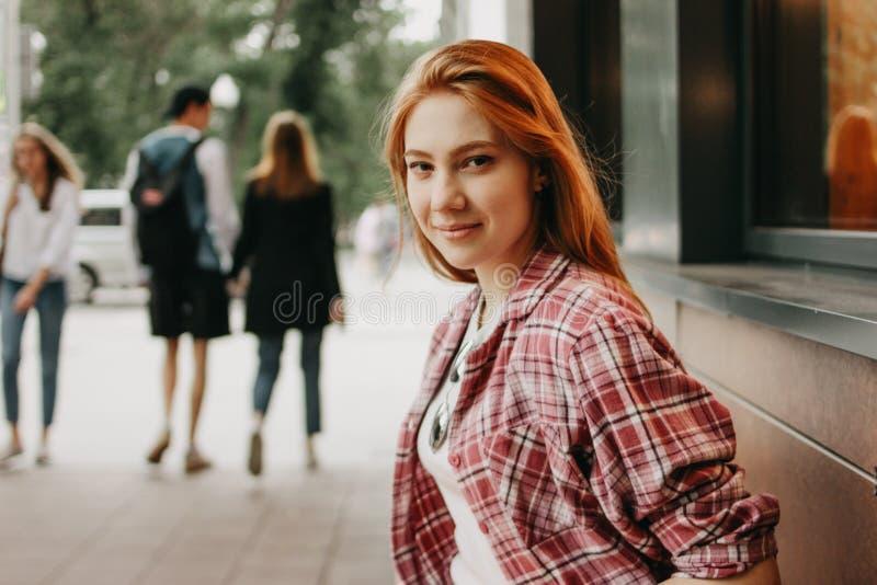 Aantrekkelijke roodharige het glimlachen studenten geklede vrijetijdskleding bij straat in stad royalty-vrije stock afbeelding