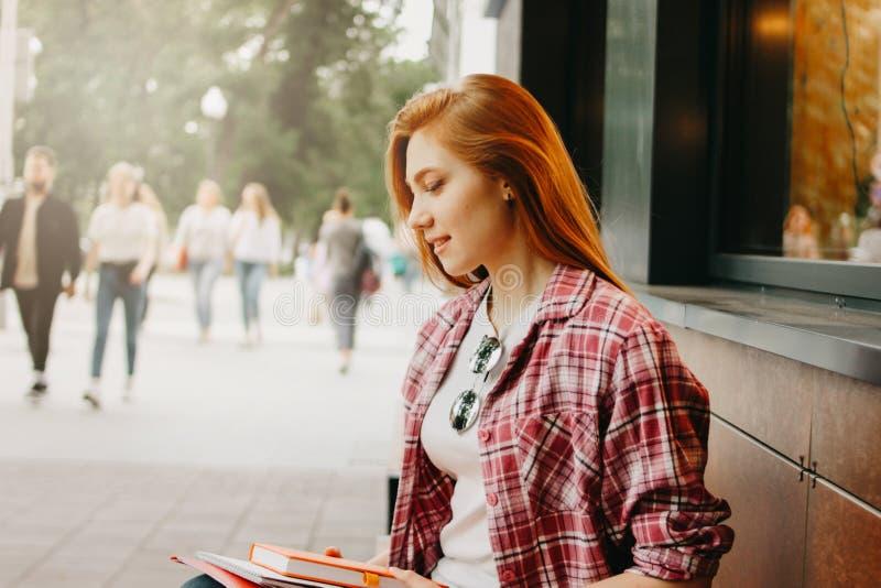 Aantrekkelijke roodharige het glimlachen studenten geklede vrijetijdskleding bij straat in stad royalty-vrije stock afbeeldingen