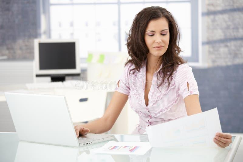 Aantrekkelijke secretaresse die in helder bureau werkt stock afbeeldingen