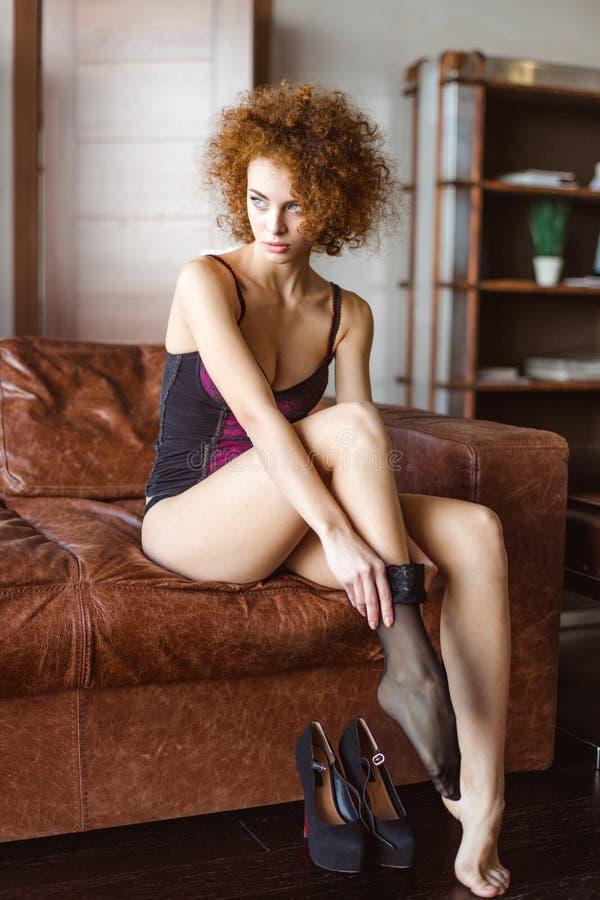 Aantrekkelijke sensuele jonge krullende vrouw in korset die zwarte kousen dragen stock foto's
