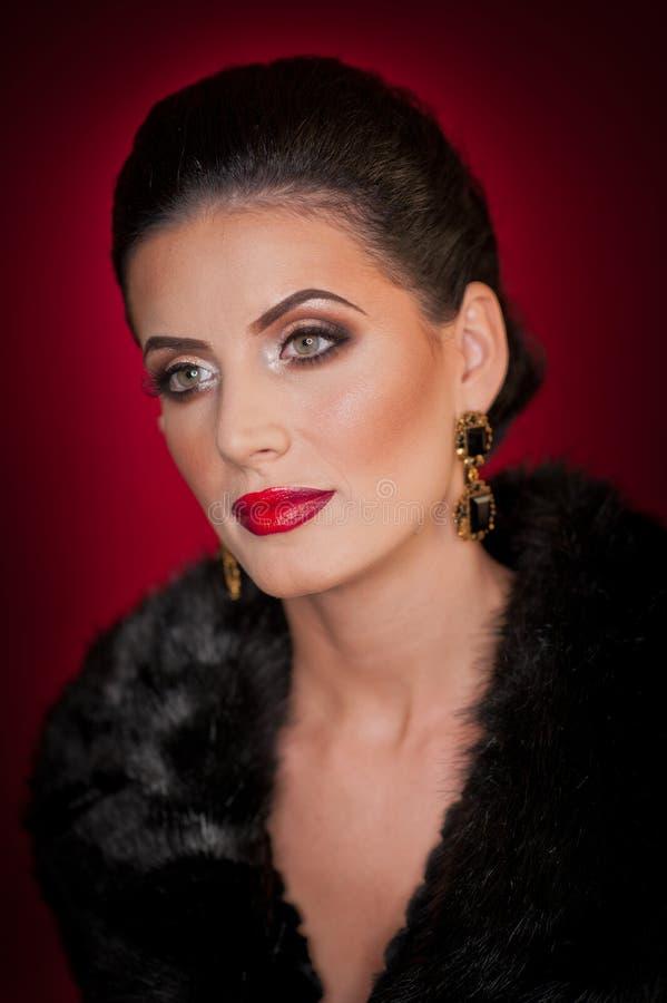 Aantrekkelijke sexy jonge vrouw die bontjas het stellen in studio op donkere purpere achtergrond dragen Portret van sensueel wijf royalty-vrije stock fotografie