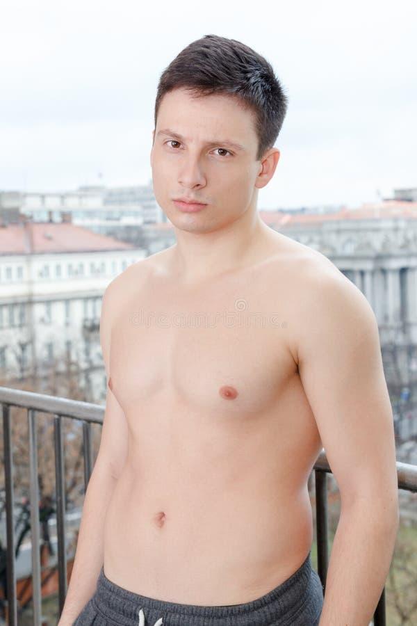Aantrekkelijke shirtless jonge nadenkende mens die in openlucht stellen stock afbeelding